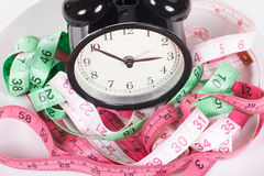 Measuring tapes and alarm clock stock images