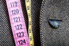 Measuring tapes and half buttoned button on jacket Stock Images