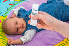 Measuring temperature to a baby with thermometer Stock Photos