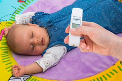 Measuring temperature to a baby with thermometer Royalty Free Stock Photo