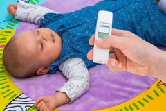 Measuring temperature to a baby with thermometer Stock Photography
