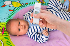 Measuring temperature to a baby with thermometer Stock Image