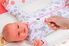 Measuring temperature to a baby with thermometer Royalty Free Stock Photography