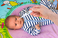 Measuring temperature to a baby with thermometer Stock Images