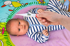 Measuring temperature to a baby with thermometer Stock Photo
