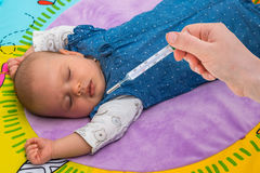 Measuring temperature to a baby with thermometer Royalty Free Stock Image