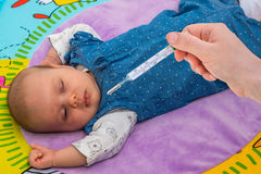 Measuring temperature to a baby with thermometer Royalty Free Stock Photos