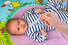 Measuring temperature to a baby with thermometer Royalty Free Stock Images