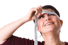 Measuring time. Pretty brunette holding the measuring tape around her head and trying to look at the numbers Royalty Free Stock Image