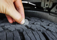 Measuring tire depth. Using a small coin stock photography