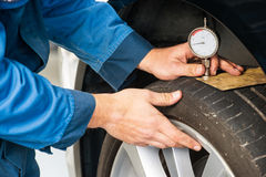 Measuring tire tread using a gauge Royalty Free Stock Image