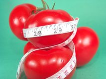 Measuring Tomatoes. High resolution digital photo of tomatoes and a measuring tape symbolize healthy diet, cancer/disease prevention and body weight control. It stock images