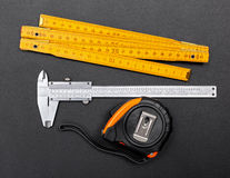 Measuring tools on black: ruler, caliper and tape. Measuring tools on black background: ruler, caliper and tape on black Stock Photos