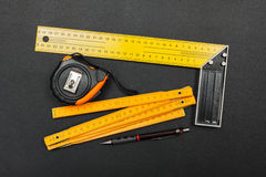 Measuring tools and pencil on black Stock Photos