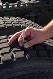 Measuring tread depth tractor-trailer truck tire. Photo is a close up view of driver's hand holding gauge used to measure tread depth of tire on tractor-trailer Royalty Free Stock Images