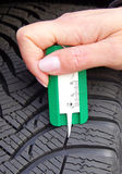 Measuring tread in winter tyre. Hand of woman using tool to measure tread depth of winter tire Royalty Free Stock Photos