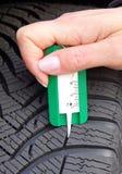 Measuring tread in winter tyre royalty free stock photos
