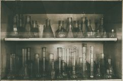 Glass tubes in the abandoned chemical laboratory. Measuring tubes in the closet of an abandoned, vintage lab Stock Photo
