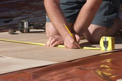 Measuring Up. Carpenter measuring using tape Stock Images