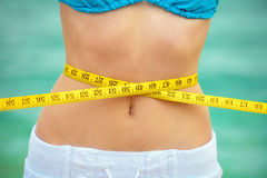 Measuring waist. Young woman measuring waist after the fitness royalty free stock photo