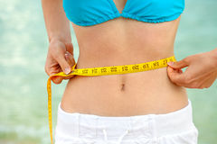 Measuring waist. Young woman measuring waist after the fitness stock photo