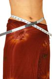 Measuring waist. Young woman measuring her waist over the white background Stock Photos