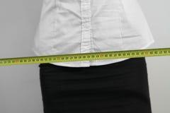 Measuring waist. The businesswoman measuring her waist Royalty Free Stock Photo