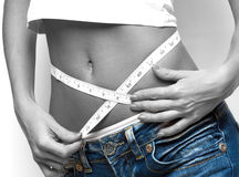 Measuring waist. Close up of a woman measuring her waist, b/w toned stock photography