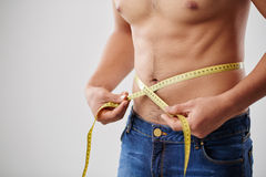 Measuring waist. Cropped image on man measuring his waist with tape Royalty Free Stock Image