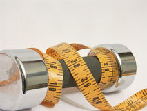 Measuring Weight. Photo of a tape measure wrapped aroound a hand weight on white background Royalty Free Stock Images