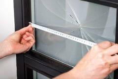 Measuring window dimension. Measuring dimension of broken window before a repairing Royalty Free Stock Photo