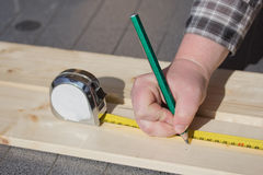 Measuring a wooden board with ruler and pencil. Stock Photography