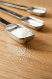 Measurings Spoons on Wood Counter with Sugar Royalty Free Stock Photo