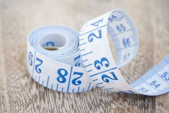 Measurring tape metter with blue figures over wooden board. Control weight, loose weight. Isoalted ribbon. Measurring tape metter with blue figures. Control royalty free stock image