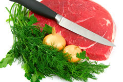 Meat. Piece of a beef, greens, knife and two onions, on white Stock Image