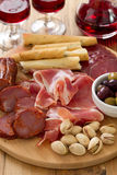 Meat appetizer with olives and nuts on tray Stock Images