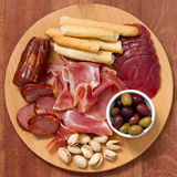 Meat appetizer with olives and nuts on tray Stock Photo