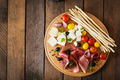 Meat appetizer on a plate. On old wooden background Royalty Free Stock Photo