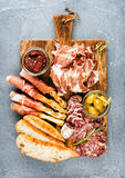 Meat appetizer selection or wine snack set. Variety of smoked meat, salami, prosciutto, bread sticks, baguette, olives Royalty Free Stock Images