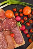 Meat appetizers next to cherry tomatoes, radish and green onion. On wooden board Stock Photography
