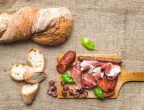 Meat appetizers selection and a loaf of rustic village bread on Stock Photos