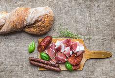 Meat appetizers selection and a loaf of rustic village bread on Royalty Free Stock Photo