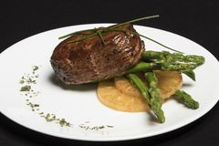 Meat with asparagus and pineapple on white plate and black background stock image