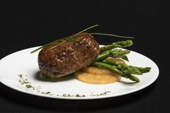 Meat with asparagus and pineapple on white plate and black background stock photos