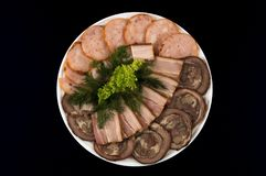 Meat, bacon and sausage, decorated with salad and dill on a dark background royalty free stock photography