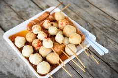 Meat ball , fish ball and sausage hotdog grilled on stick on tray with wooden background Thai style food. Meat ball , fish ball and sausage hotdog grilled in royalty free stock photography