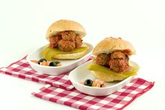 Meat Ball Sandwiches for two. Crusty bun filled with beef meat balls, a chilli pepper and a tomatoe olive chilli side royalty free stock image