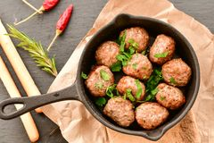 Meat balls  in vintage cast-iron pan. Meat balls in a cast iron pan with grissini  and  herbs on wooden rustic background top view close up, black pepper , red Stock Images