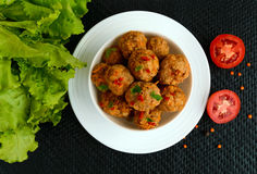 Meat balls with chilli and herbs in a white bowl on a black background. Royalty Free Stock Images