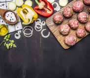 Meat balls with herbs and onions on a cutting board with vegetables, spices, oil, vintage wooden spoon on wooden rustic background Stock Images